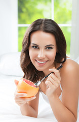 Smiling young woman eating grapefruit at home