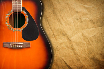 Acoustic guitar resting against a blank grunge background with c