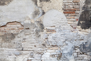 Old brick wall with damaged stucco and paint layers