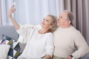 Happy mature couple taking photo of their self with mobile phone at home