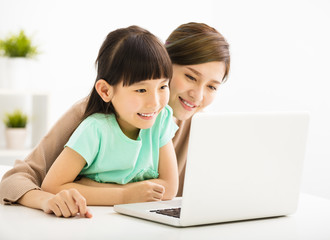happy Little girl looking at laptop  with her mother