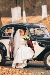 Beautiful happy bride with bouquet near retro car in autumn