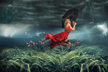 girl in red dress running away from the storm