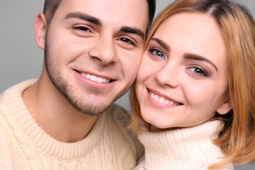 Young couple in love embracing on grey background