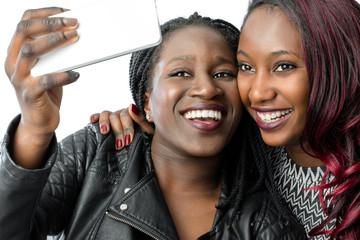 African teen girls taking selfie with smart phone.