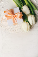 Bouquet of fresh tulips and present box on wooden table, top view