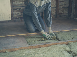 Young woman laying insulation in loft