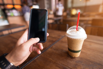 Hand holding mobile phone with class of iced cappuccino on the table, coffee shop background, warm tone