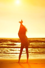 Silhouette full length young woman on beach with arms raised