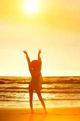 Silhouette young woman at beach with hands raised