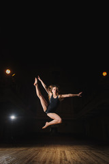 Young brunette dancer girl in split jump