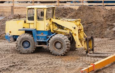 Ein schwerer gelber Radlader mit Gabel steht in einer Baugrube