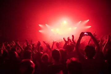 Applauding crowd at a live dj performance with red light