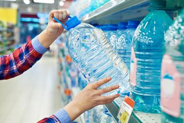 Woman buys bottle drinking water in shop