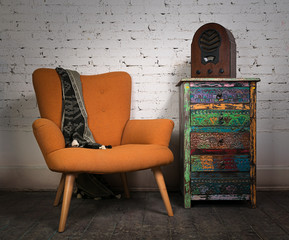 Vintage orange armchair, colorful cupboard and aged wooden radio