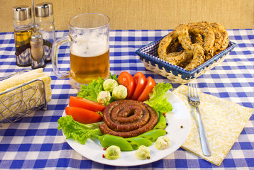 Still life of a plate with grilled sausages, beer and bretzel