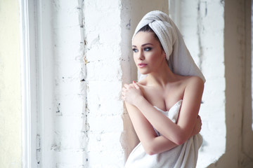 beautiful thoughtful girl in a towel after a shower near the window