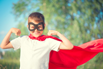 Little boy wearing superhero costume and having fun outdoors