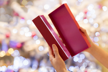 Woman opens a red gift in front of a Christmas tree
