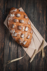 Homemade bread and ripe ears of rye on a wooden background