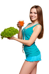 Happy teen girl holding a glass of carrot juice