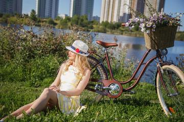 Beautiful sweet blonde woman walks with bicycle near skyscrapers