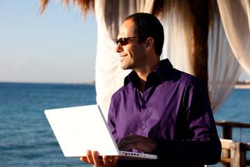 homme d'affaire en voyage avec son ordinateur au bord de la mer
