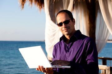 portrait d'homme d'affaire en voyage avec son ordinateur au bord de la mer