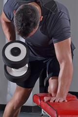 Hombre entrenando con una pesa de gimnasio.