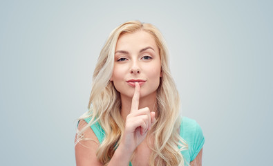 beautiful young woman holding finger at her lips