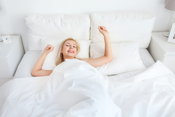 young woman stretching in bed at home bedroom