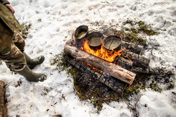 Cooking in a winter hike in the cauldron hanging over the fire in the snow-covered pine forest while camping on a sunny day, man stands near