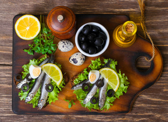 Traditional Spanish sandwiches with anchovies, lettuce and lemon on a wooden background