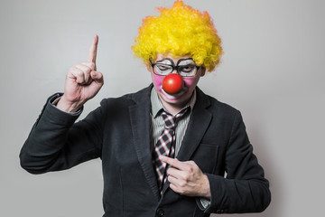 clown, with his finger raised to the top as a gesture of attracting attention dressed as a businessman