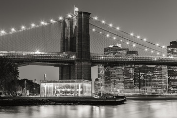 Wall Mural - Black and White of  Brooklyn Bridge Tower at twilight with carousel and skyscrapers of Lower Manhattan. Financial District. New York City