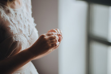 Wedding. Bride. Preparations. Wedding Dress. Bride in cream-colored lace dress stands in front of the window with her hands folded