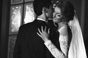 Sensual groom kissing beautiful bride, face closeup b&w