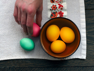 Easter eggs in a bowl on the table. Eggs are yellow, pink and green. Easter still life. A man's hand takes an egg