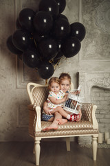 Happy little sisters with black balloons. Stock photo.
