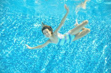Child swims in pool underwater, happy active girl jumps, dives and has fun under water, kid sport on family vacation