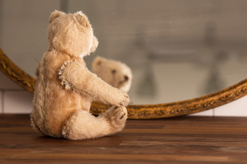 An old grey teddy bear is sitting and looking at him selves in the mirror on a wooden bench with tiles in the background