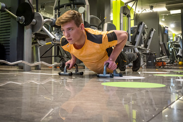Young man in a gym doing push-ups on the floor
