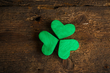 Green shamrock clovers on wooden background