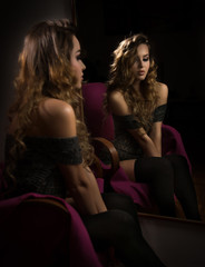 Attractive sexy blonde with black long stockings posing sitting in front of a mirror. Portrait of sensual young woman exposing her shoulders. Beautiful girl with long curly hair, reflection photo