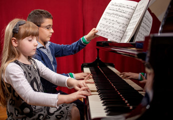 young pianists,boy and girl playing a grand piano