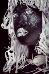 creative makeup like Ethiopian mask, white pattern on black face close up, halloween horror