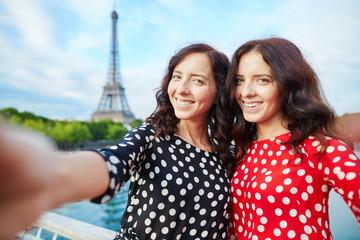 Beautiful twin sisters taking selfie