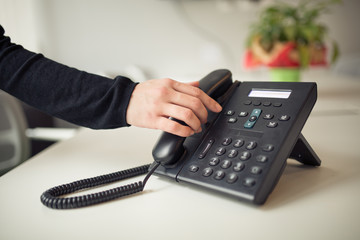 Answering phone call.Phone ringing.Good or bad news.Business failure.Customer service help center.Secretary answering phone in her office.Desk table office phone and womans hand picking up