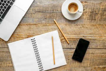 Working place with coffee cup, laptop, phone on wooden table