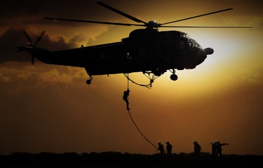 Helicopter dropping soldier during sunset